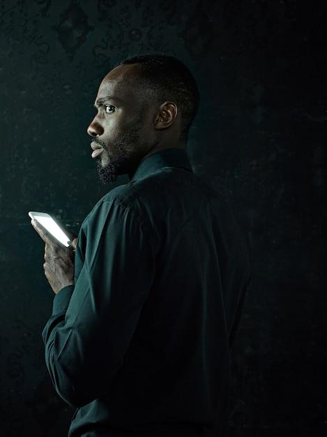 Studio shot van jonge ernstige zwarte afrikaanse man denken tijdens het praten op de mobiele telefoon tegen zwarte studio achtergrond Gratis Foto
