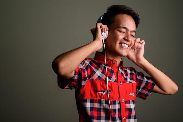 Studio shot van jonge tiener man met rood geruit overhemd tegen gekleurd Premium Foto