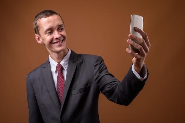 Studio shot van jonge zakenman op bruin Premium Foto