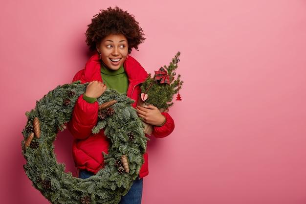 Studio shot van mooie donkere huid model draagt kerstkrans en versierde dennenboom, heeft een feestelijke stemming, draagt rode bovenkleding, geïsoleerd op roze achtergrond Gratis Foto