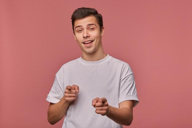 Studio shot van mooie donkerharige jonge man hand opsteken en met wijsvingers vooruit wijzen, staande over roze achtergrond in vrijetijdskleding, zelfverzekerd naar camera kijken en glimlachen Gratis Foto