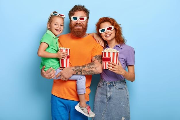 Studio shot van mooie roodharige paar hebben weekend, ga naar de bioscoop om een nieuwe film te kijken, draag een stereobril, eet fastfood Gratis Foto