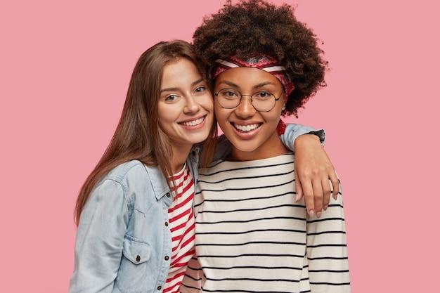 Studio shot van mooie twee jonge gelukkig gemengd ras vrouwen staan dicht bij elkaar Gratis Foto