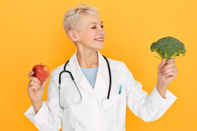 Studio shot van vriendelijke positieve blonde rijpe vrouwelijke arts poseren geïsoleerd met verse broccoli en appel in haar handen, adviserend meer groente en fruit te eten. gezond eten, diëten en voeding Gratis Foto