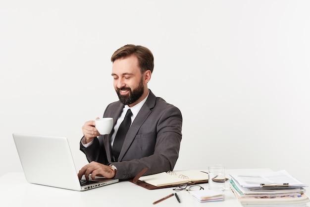 Studio shot van vrolijke bebaarde brunette man in formele kleding werken op kantoor met laptop en zijn aantekeningen, hand en toetsenbord houden terwijl het hebben van een kopje koffie Gratis Foto