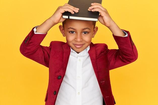 Studiobeeld van vrolijke stijlvolle donkere scholier met plezier, zwarte notitieboekje op het hoofd houden, camera kijken met een blije glimlach. Gratis Foto