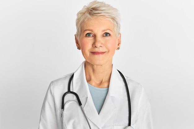 Studiobeeld van zelfverzekerde aantrekkelijke vrouwelijke arts van middelbare leeftijd met kort geverfd kapsel poseren geïsoleerd met witte jas en stethoscoop. Gratis Foto