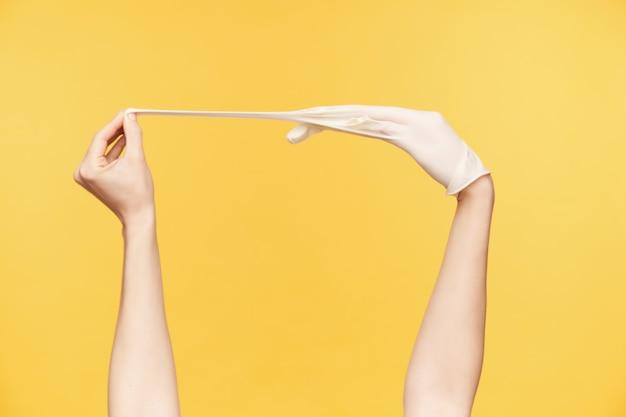 Studiofoto van de handen van de jonge vrouw die zich voordeed op een oranje achtergrond, een hand die middelvinger trekt terwijl ze een witte rubberen handschoen tevoorschijn haalt. menselijke handen concept Gratis Foto