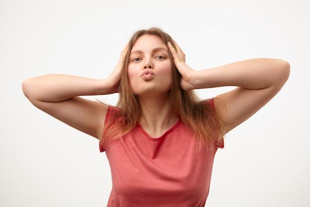 Studiofoto van jonge blonde dame met losse lange haren die haar lippen in luchtkus vouwen en hoofd met opgeheven handen vasthouden terwijl zij op witte achtergrond staat Gratis Foto