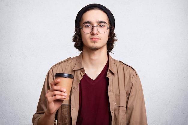 Studioportret van de ernstige mens met kop van hete aromatische koffie. Gratis Foto