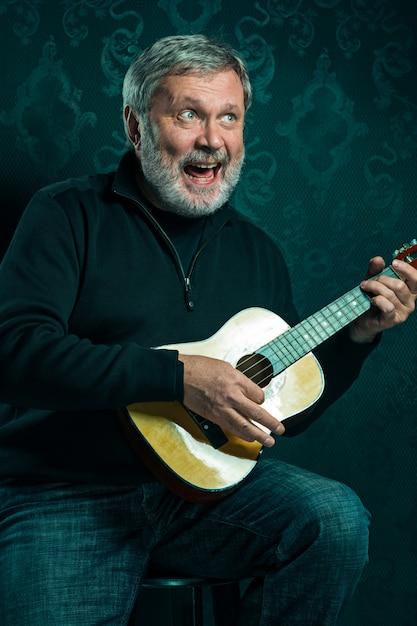 Studioportret van de hogere mens met kleine gitaar op zwarte studio Gratis Foto