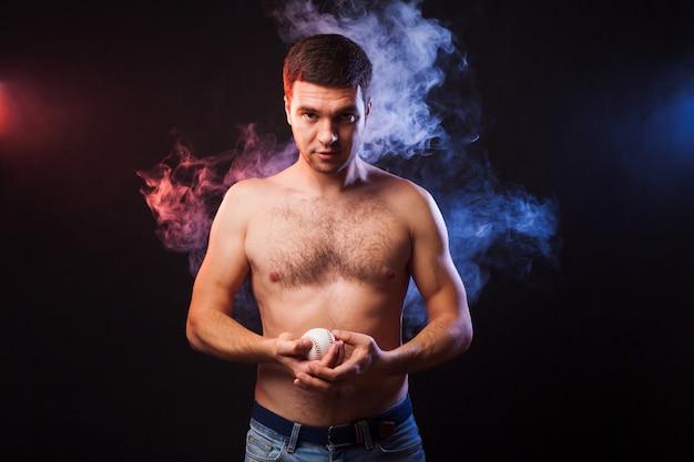 Studioportret van gespierde sportman met speler het stellen op zwarte achtergrond in gekleurde rook met honkbal in zijn hand. Premium Foto
