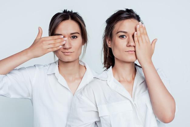 Studioportret van jonge vrouwelijke tweelingenzusters op grijs Gratis Foto