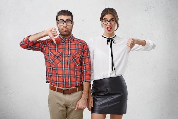 Studioportret van wankele man en vrouw uiten afkeer, afkeuring of minachting Gratis Foto