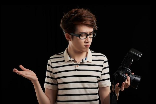 Studioschot van de aziatische mens tegen zwarte achtergrond die het camerascherm bekijken en hulpeloos gebaar met zijn handen maken Gratis Foto
