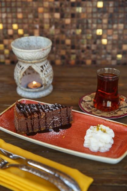 Stuk chocolade brownie geserveerd met room en thee Gratis Foto