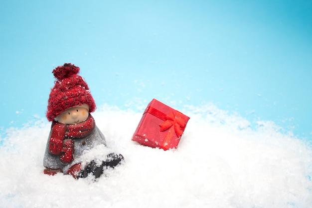 Stuk speelgoed kerstmiself zit in de sneeuw, copyspace Premium Foto