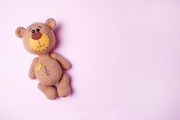 Stuk speelgoed teddybeer op een roze achtergrond wordt geïsoleerd die. baby achtergrond. kopieer ruimte, bovenaanzicht. Premium Foto