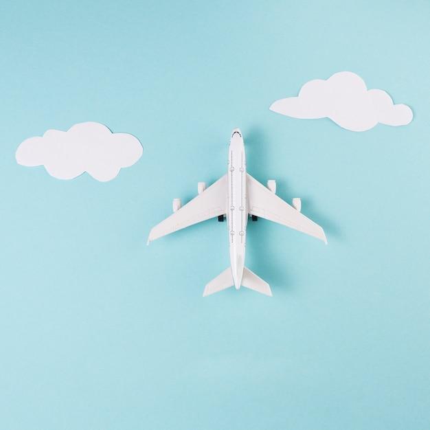 Stuk speelgoed vliegtuig en wolken op blauwe achtergrond Gratis Foto