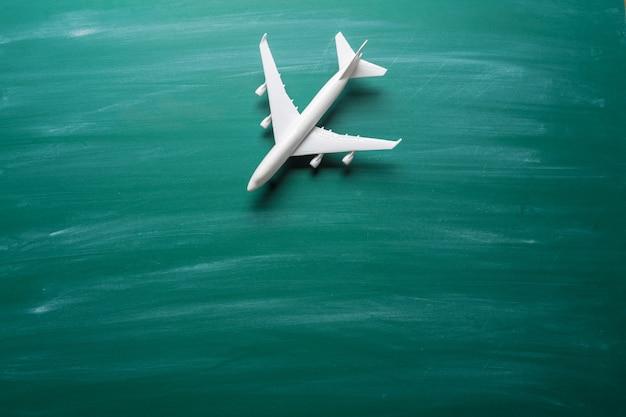 Stuk speelgoed vliegtuig over bordachtergrond Premium Foto