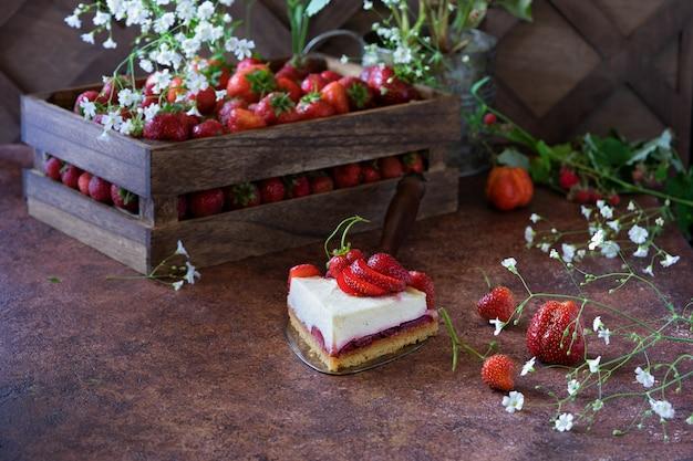 Stuk van aardbeikaastaart en houten doos met verse aardbeibessen en witte bloemen op bruin Premium Foto