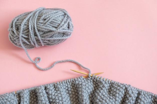 Stuk van grijze gebreide stof op de naalden met bal van garen, proces om op roze achtergrond te breien. Premium Foto