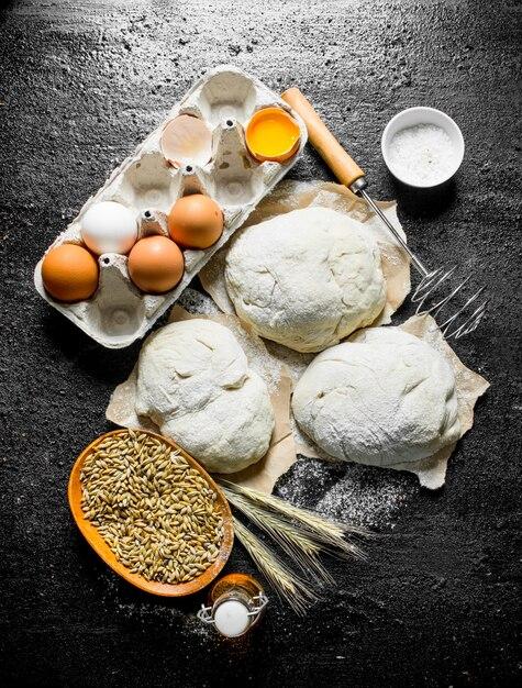 Stukjes deeg met garde, eieren en graan in de kom. op zwarte rustieke ondergrond Premium Foto