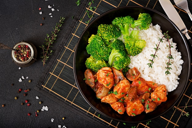 Stukjes kipfilet met champignons gestoofd in tomatensaus met gekookte broccoli en rijst. goede voeding. gezonde levensstijl. dieetmenu. bovenaanzicht Gratis Foto