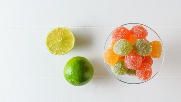 Stukjes kleurrijke marmelade in een glazen kom en limoen op een witte tafel. heerlijke snoepjes gemaakt van gelei met suiker. het uitzicht vanaf de top. Premium Foto