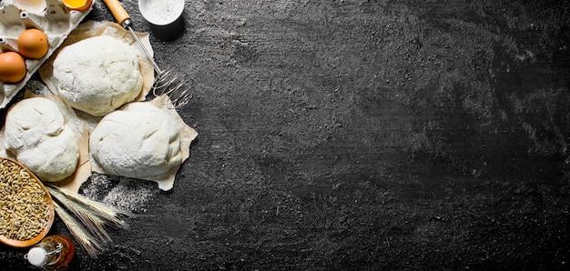 Stukken deeg met een garde, eieren en graan in de kom op zwarte rustieke tafel Premium Foto