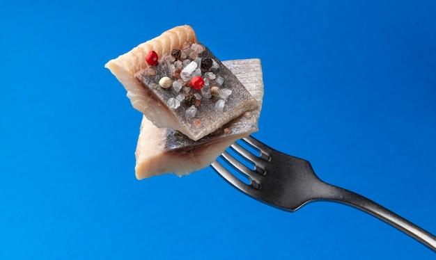 Stukken gezouten haring op vork geïsoleerd op blauw Premium Foto