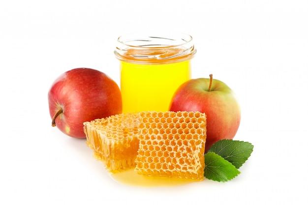 Stukken van honingraat, appels en glazen pot geïsoleerd op wit Premium Foto