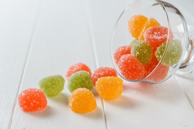 Stukken van kleurrijke marmelade gegoten uit een glazen kom op een witte tafel. heerlijke snoepjes gemaakt van gelei met suiker. Premium Foto