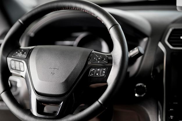 Stuurwiel close up in een nieuwe auto, airbag, cruise control, ruitenwisserschakelaar en een modern dashboard Premium Foto