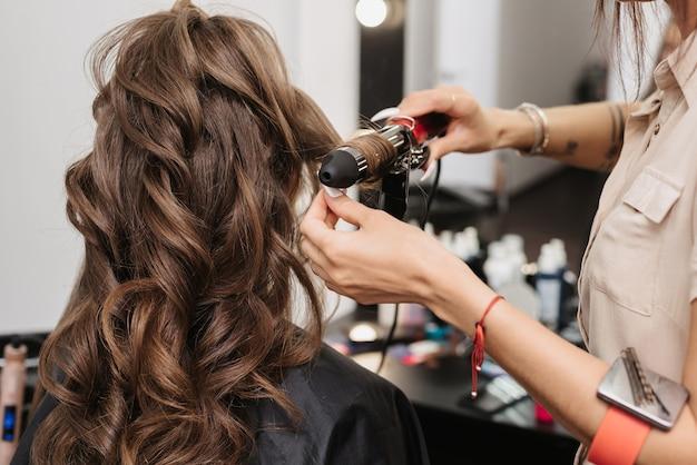 Stylist maakt krullen van een vrouw met lang bruin haar in een professionele schoonheidssalon Premium Foto