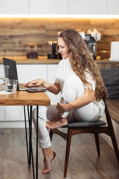 Succesvol en meisje dat thuis lacht werkt. mooie modieuze en vrouw die thuis glimlachen ontspannen. zakenvrouw ondernemer werken op laptop vanuit kantoor aan huis Premium Foto