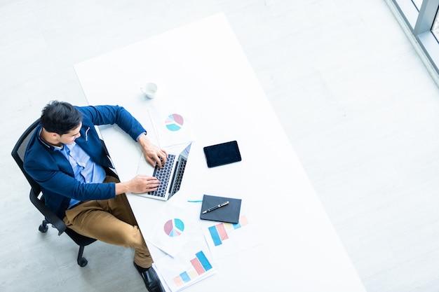 Succesvol van aziatische jonge zakenman die met hand het typen toetsenbord op laptopcomputer werkt, tablet met het lege geïsoleerde aanrakingsscherm en pen op notitieboekje op witte houten lijst in bureau Premium Foto