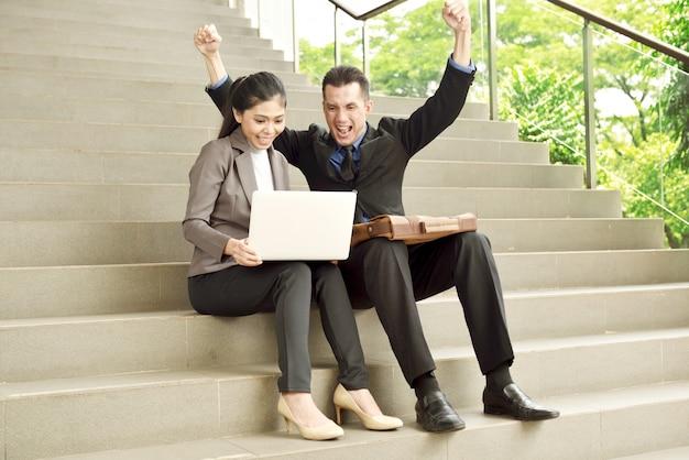 Succesvolle aziatische bedrijfsmensen die met laptop zeer gelukkig kijken Premium Foto