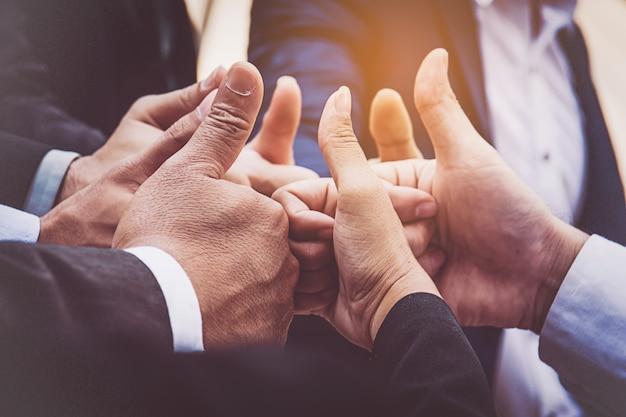 Succesvolle bedrijfsmensen met duimen omhoog en glimlachend, commercieel team Premium Foto