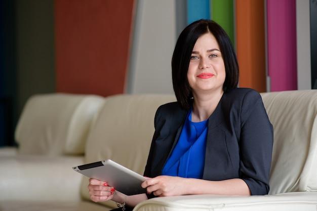 Succesvolle bedrijfsvrouw die met computer en tablet werkt. Premium Foto