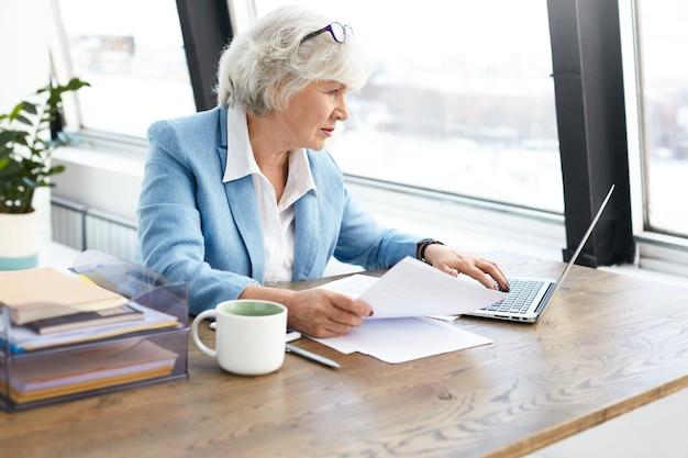 Succesvolle ervaren oudere vrouwelijke advocaat mooi pak en bril dragen op haar hoofd met behulp van draagbare computer op haar werkplek, scherm kijken met gerichte geconcentreerde gezichtsuitdrukking Gratis Foto