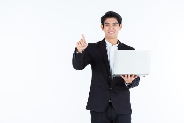 Succesvolle gelukkig van aziatische jonge zakenman een succesvolle laptop van de bedrijfsgreep computer met het richten van de de vingeraanraking van handgebaren geïsoleerd beeldmateriaalpaneel Premium Foto