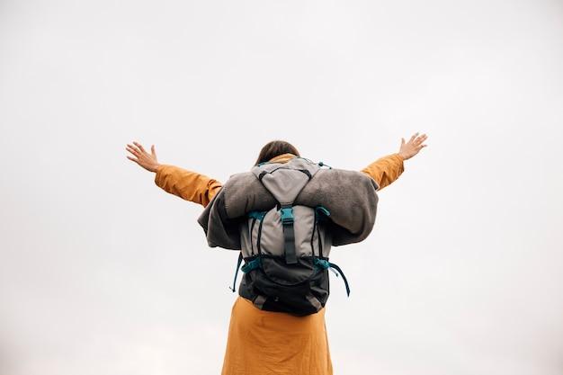 Succesvolle jonge vrouwen backpacker open wapens tegen hemel Premium Foto