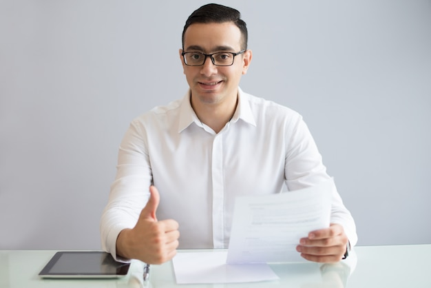Succesvolle jonge zakenman met document duimen opdagen Gratis Foto