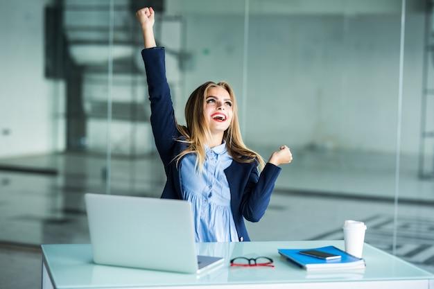 Succesvolle jonge zakenvrouw met armen omhoog op kantoor Gratis Foto