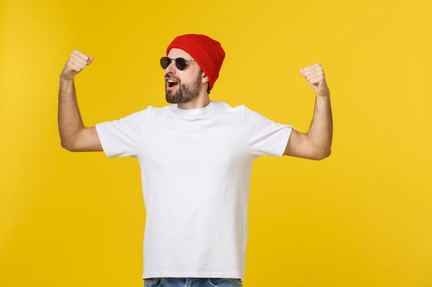 Succesvolle jongeman vieren tegen een gele ruimte Premium Foto