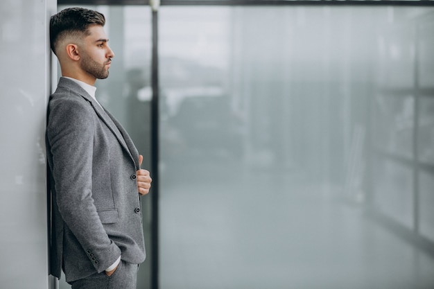 Succesvolle knappe zakenman in een kantoor Gratis Foto