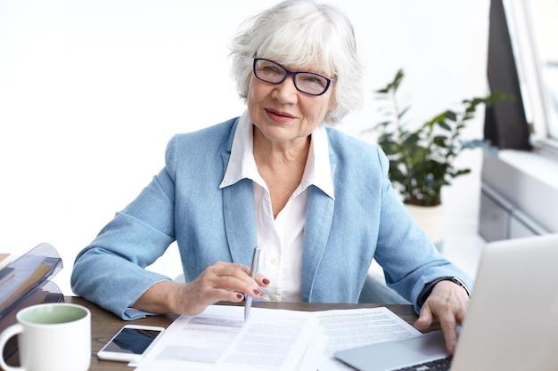 Succesvolle stijlvolle volwassen vrouwelijke chief executive officer dragen van een bril en formele kleding kijken door financieel verslag, werken bij bureau, met behulp van elektronische gadgets en maken van aantekeningen Gratis Foto