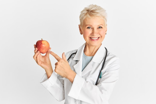 Succesvolle vrouw arts van middelbare leeftijd die medische unifrom draagt die naar de camera glimlacht en de wijsvinger wijst naar rijpe rode appel die goed is voor de darmgezondheid en gewichtsverlies bevordert. gezondheidszorg en voeding Gratis Foto