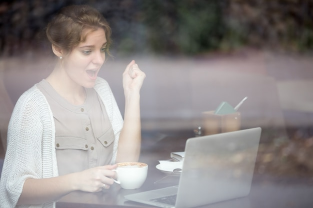 Succesvolle vrouw die met haar laptop Gratis Foto